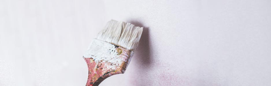 An example of a paintbrush being used by a decorator to paint a white wall